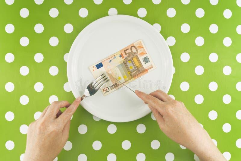 Vrouw die vijftig euroes banknotel voor diner eten stock foto