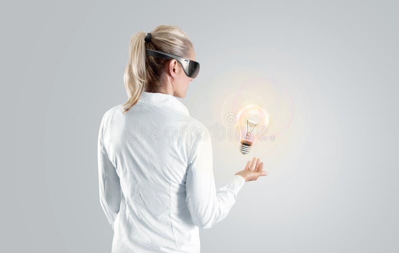 Vrouw die in virtuele werkelijkheidsglazen aan het geïsoleerde hologram kijken, royalty-vrije stock afbeeldingen