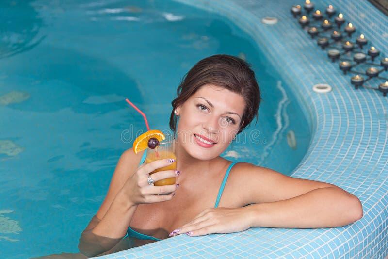 Vrouw die vitamine van dranken in Jacuzzi geniet stock foto's