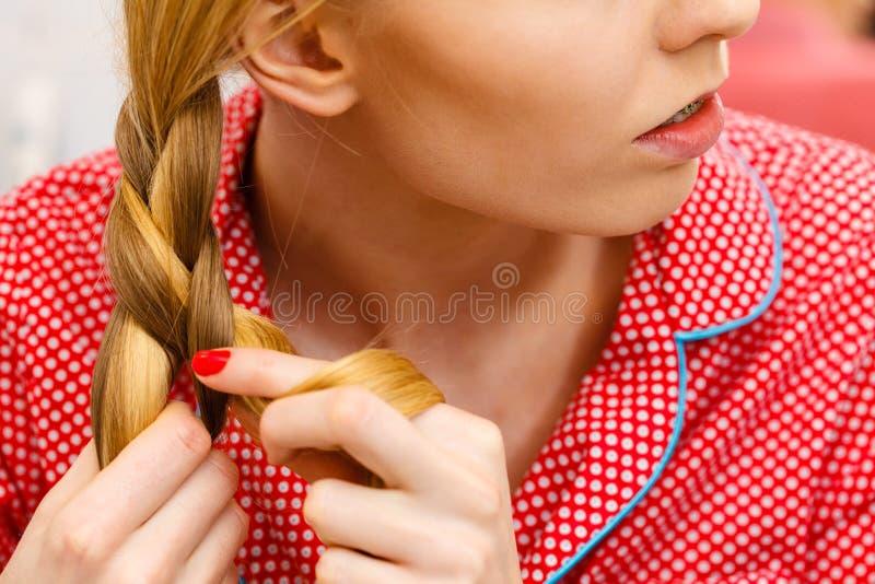 Vrouw die vlecht op blondehaar doen stock foto