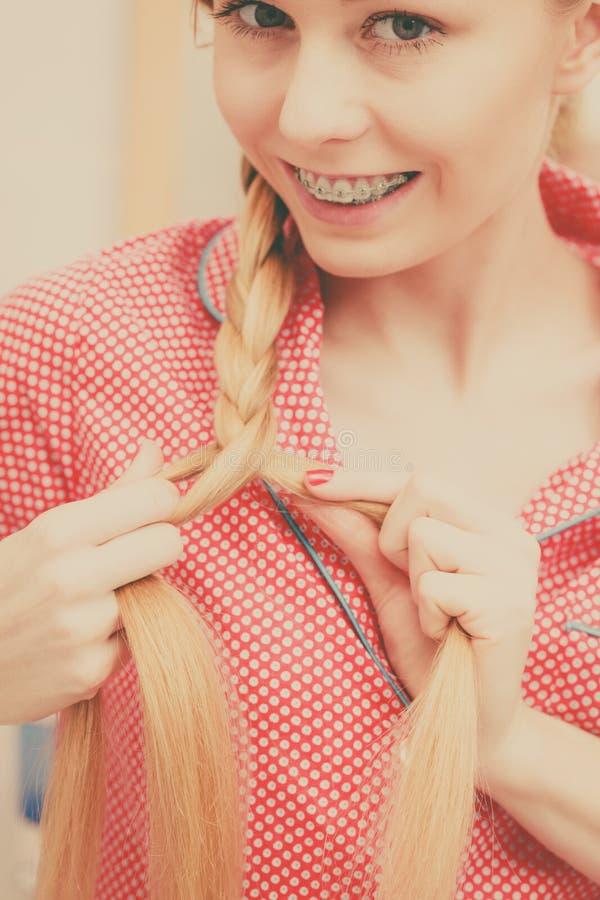 Vrouw die vlecht op blondehaar doen stock foto's