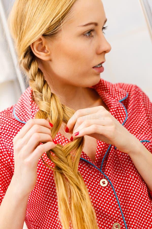Vrouw die vlecht op blondehaar doen stock fotografie