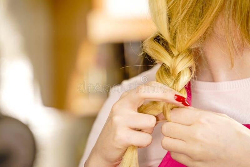 Vrouw die vlecht op blondehaar maken royalty-vrije stock foto's