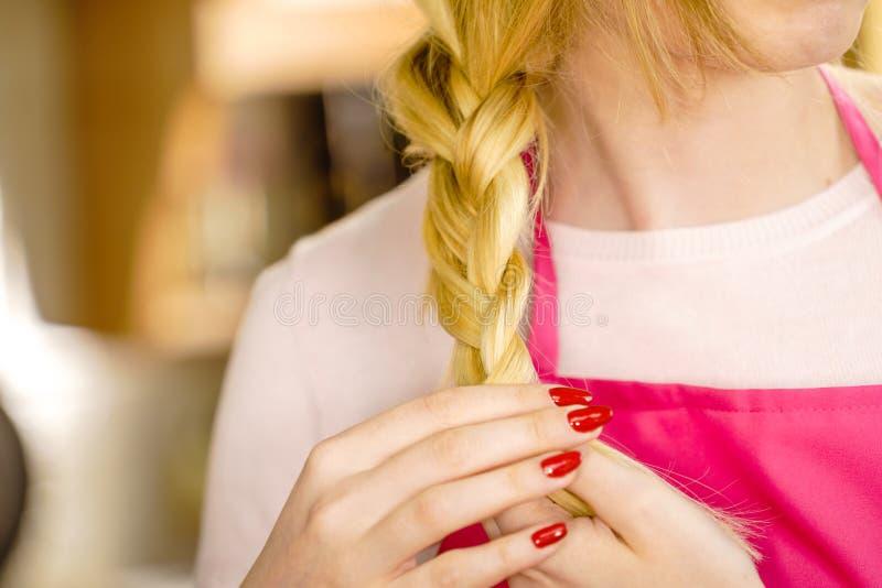 Vrouw die vlecht op blondehaar maken royalty-vrije stock foto