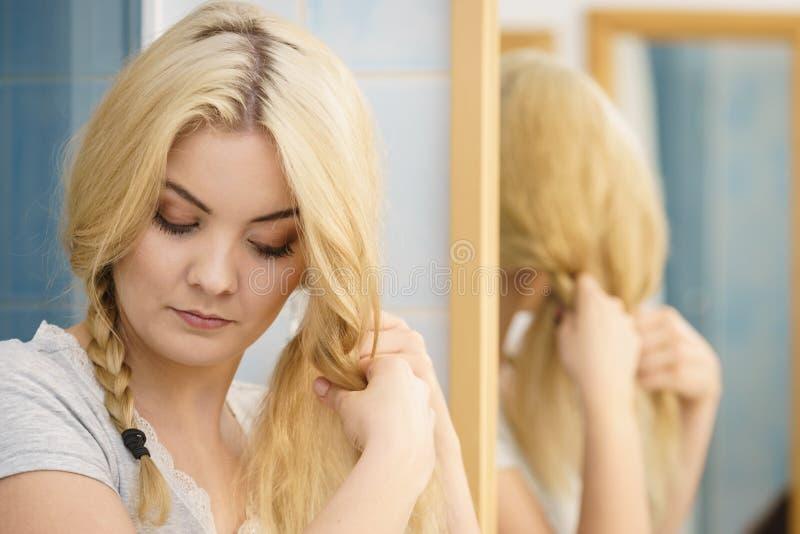 Vrouw die vlecht op blondehaar maken stock foto