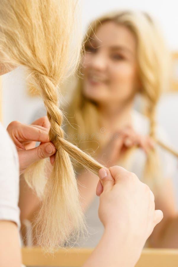 Vrouw die vlecht op blondehaar maken royalty-vrije stock afbeeldingen