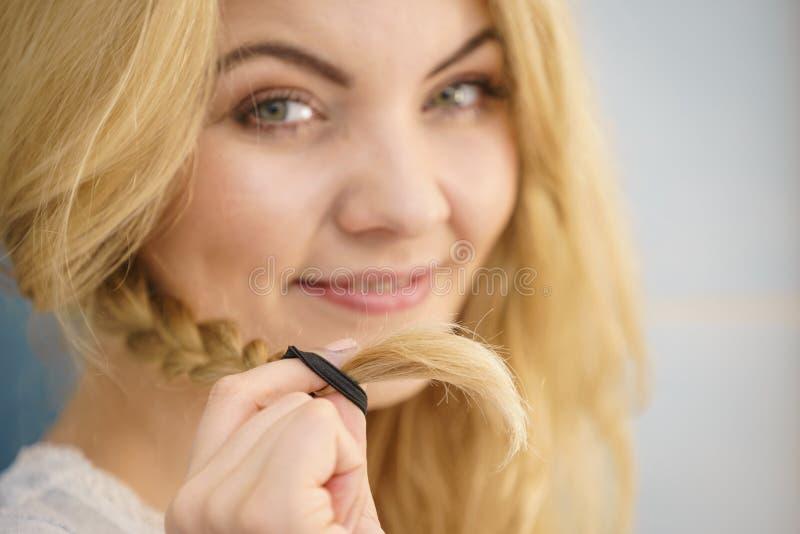Vrouw die vlecht op blondehaar maken royalty-vrije stock afbeelding