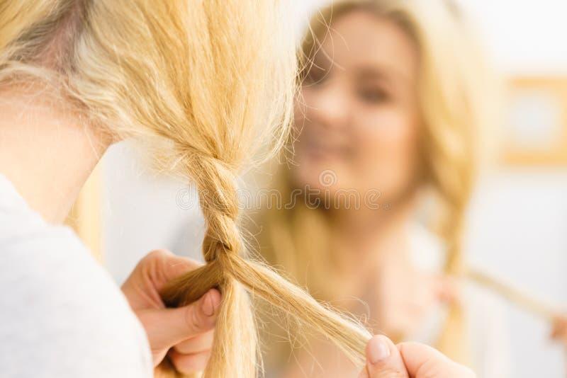 Vrouw die vlecht op blondehaar maken royalty-vrije stock fotografie
