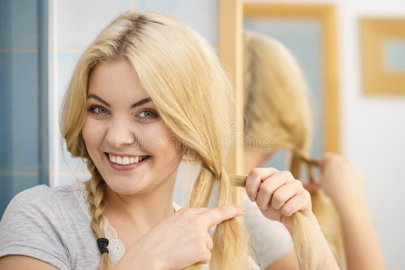 Vrouw die vlecht op blondehaar maken stock afbeelding
