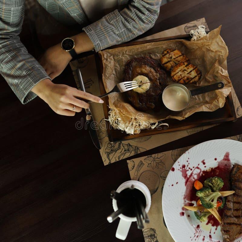 Vrouw die vleeslapje vlees met groenten in een restaurant eten Gezond en smakelijk voedsel Close-up van vrouwelijke handen Hoogst stock foto's