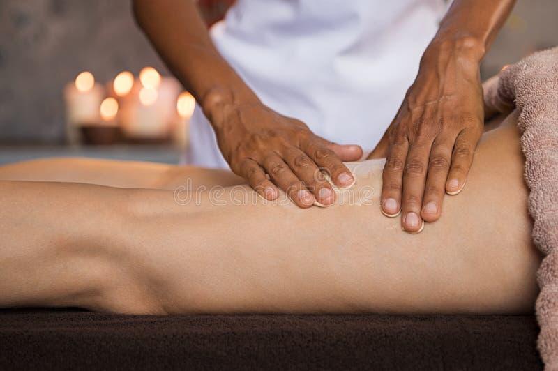 Vrouw die vochtinbrengende crème aanvragen beenmassage stock foto