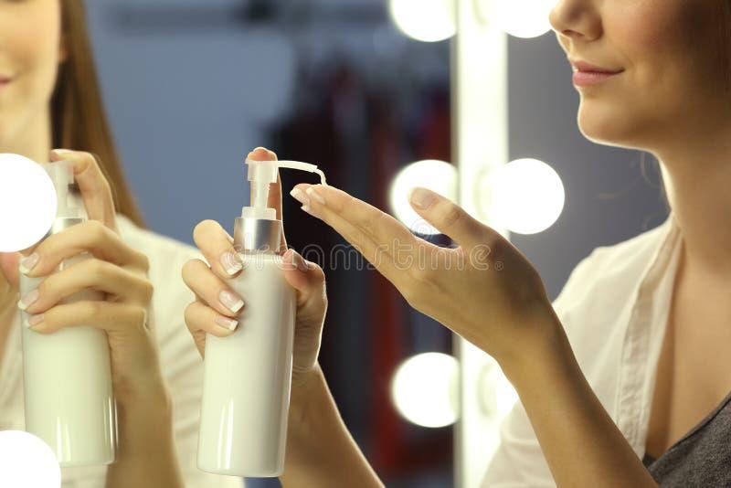 Vrouw die vochtinbrengende crèmeroom op handen toepassen royalty-vrije stock afbeeldingen