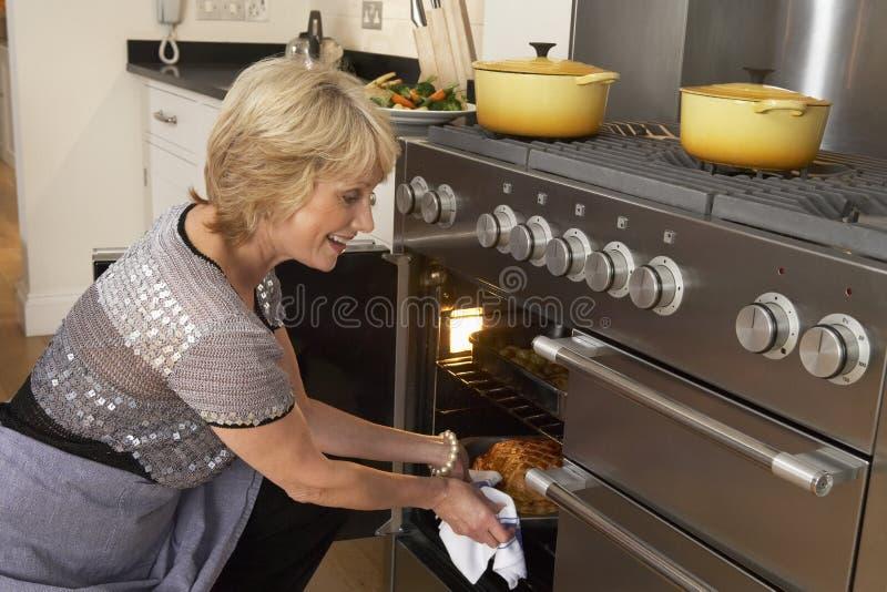 Vrouw die Voedsel neemt uit de Oven royalty-vrije stock foto