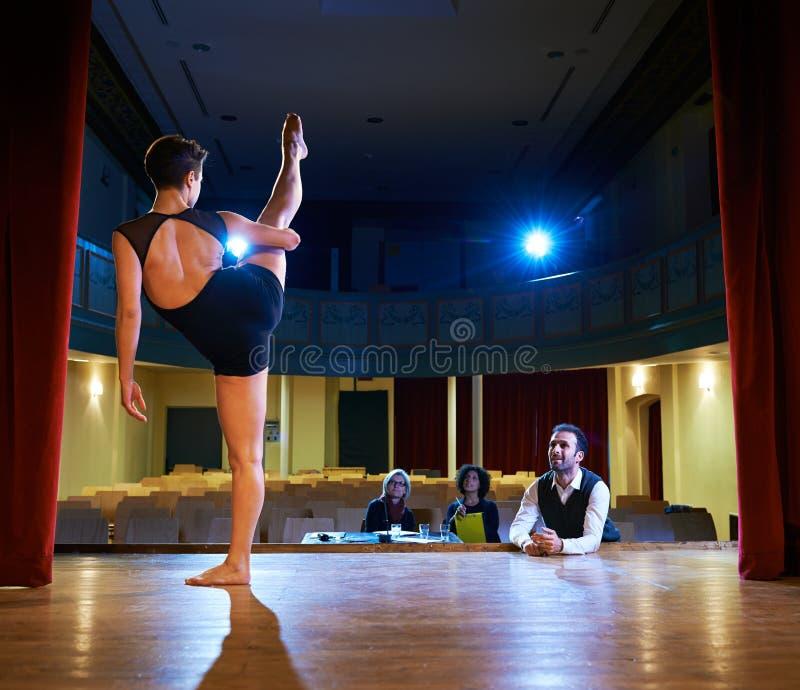 Vrouw die voor auditie met jury in theater dansen stock foto