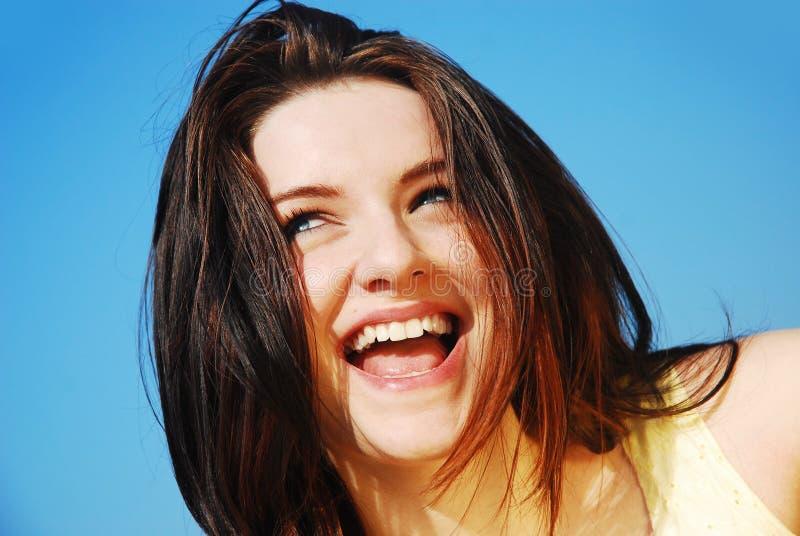Vrouw die voor blauwe hemel lacht stock foto