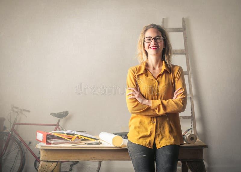 Vrouw die voor bureau glimlachen royalty-vrije stock foto's