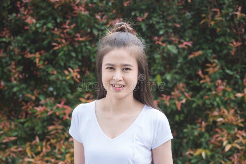 Vrouw die voor verlofmuur glimlachen in tuin stock fotografie
