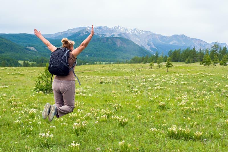 Vrouw die voor vreugde springen die de schoonheid van aard bekijken royalty-vrije stock foto's
