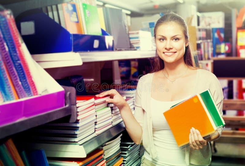 Vrouw die voorbeeldenboeken kiezen stock foto