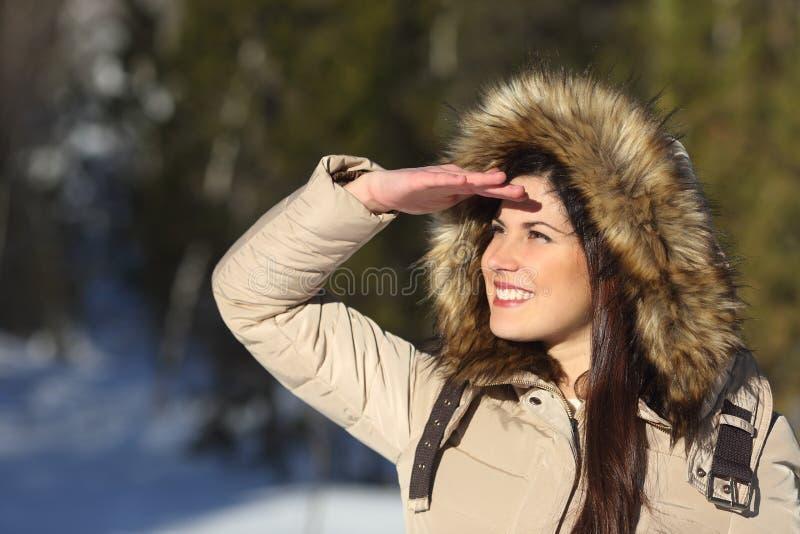 Vrouw die vooruit met de hand op voorhoofd in een bos kijken royalty-vrije stock fotografie