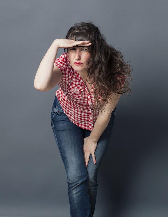 Vrouw die vooruit met hand op voorhoofd leunen om te onderzoeken stock fotografie