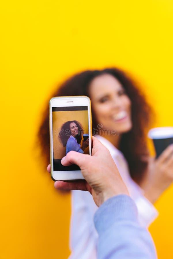 Vrouw die vriend met mobiele telefoon fotograferen stock foto