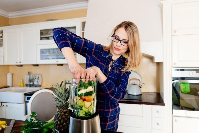 Vrouw die vruchten en groenten zetten in de eletrical mixer stock afbeelding