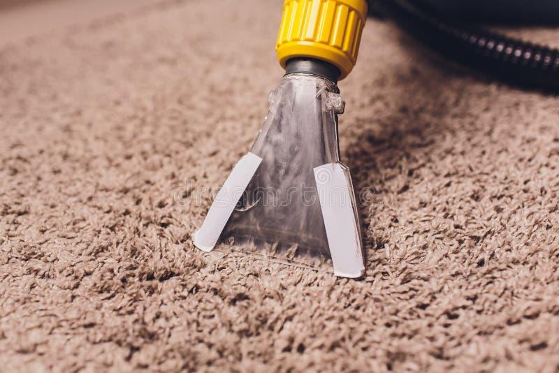 Vrouw die vuil verwijderen uit tapijt met stofzuiger in ruimte royalty-vrije stock afbeeldingen