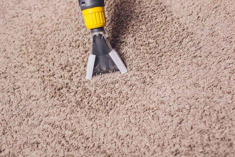 Vrouw die vuil verwijderen uit tapijt met stofzuiger in ruimte stock foto's