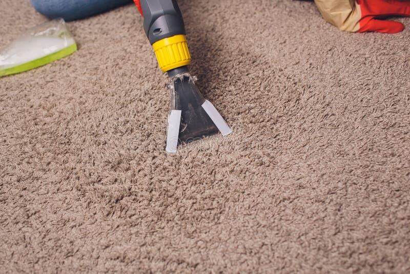 Vrouw die vuil verwijderen uit tapijt met stofzuiger in ruimte stock afbeelding