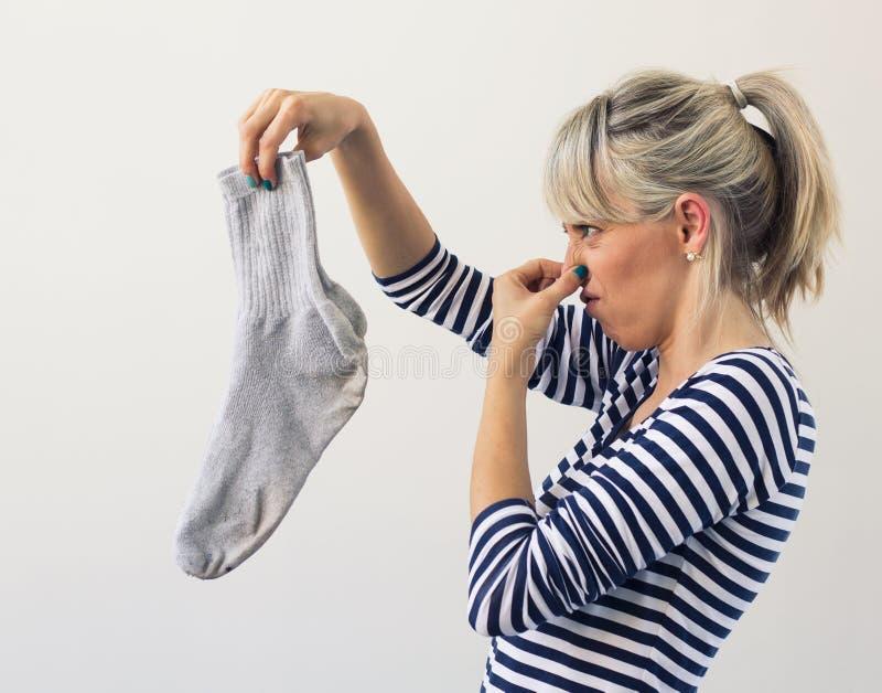Vrouw die vuile sokken houden stock foto's
