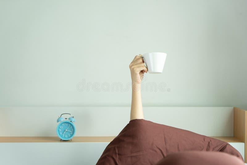 Vrouw die die wapen tonen op de kop van de holdingskoffie op bed onder dekbed in de bedruimte, Jong meisje met hand het plakken u stock afbeeldingen