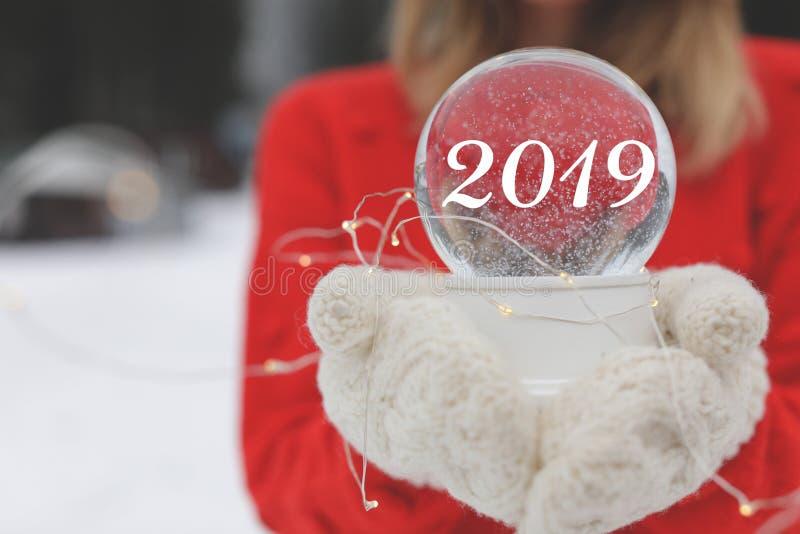 Vrouw die in warme gebreide vuisthandschoenen van sneeuwbol en Kerstmis lichten houden in openlucht, ruimte voor tekst stock foto