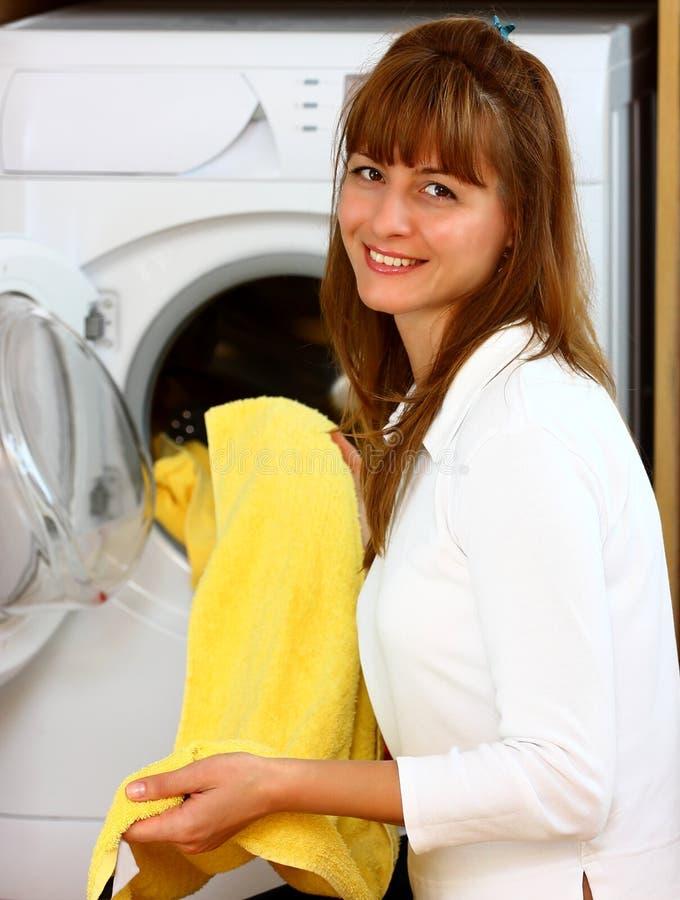 Vrouw die wasserij met glimlach doet stock foto's