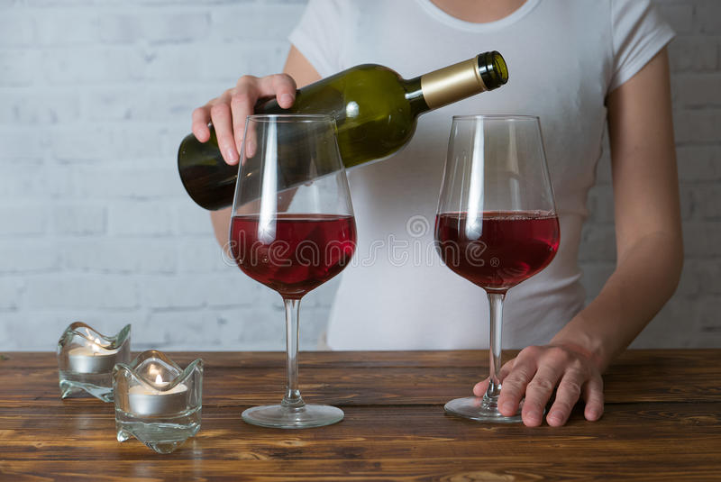 Vrouw die wat rode wijn gieten in haar glas bij romantische partij met vriend royalty-vrije stock afbeelding