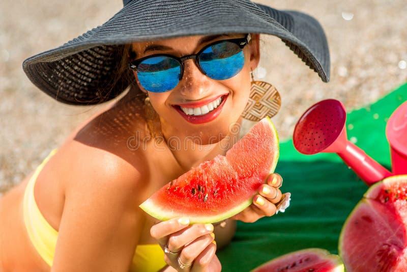Vrouw die watermeloen op het strand eet royalty-vrije stock afbeelding