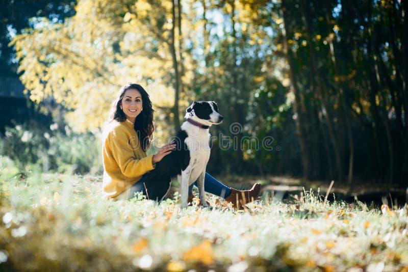 Vrouw die weekend van vrije tijd met haar hond in de herfst genieten stock afbeelding