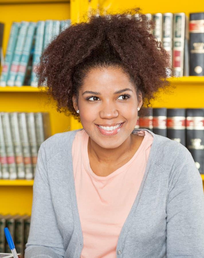 Vrouw die weg terwijl het Glimlachen op Universiteit kijken royalty-vrije stock foto's