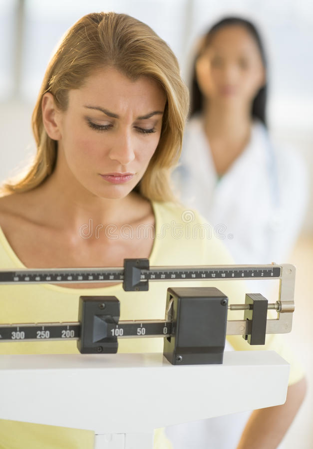 Vrouw die wegen op Tegengewichtschaal bij Kliniek stock afbeeldingen