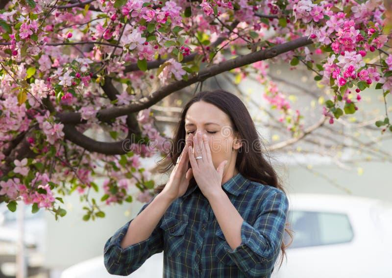 Vrouw die wegens de allergie van het de lentestuifmeel niezen stock afbeeldingen