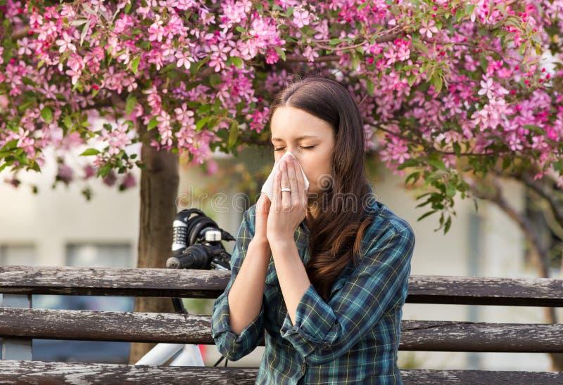 Vrouw die wegens de allergie van het de lentestuifmeel niezen royalty-vrije stock foto's