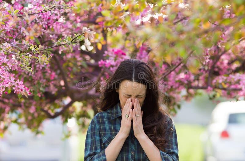 Vrouw die wegens de allergie van het de lentestuifmeel niezen stock foto's