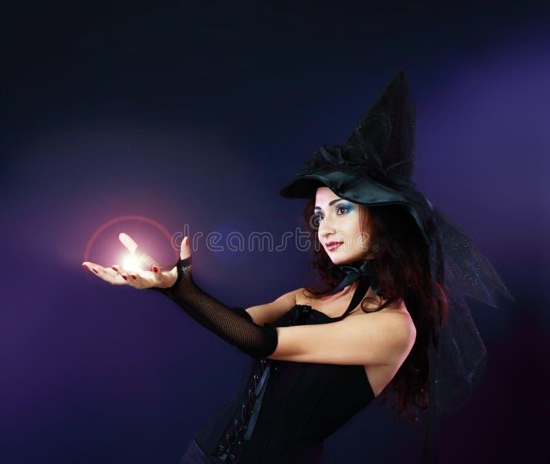 Vrouw die werktijd met magische vuurbol maakt stock afbeeldingen