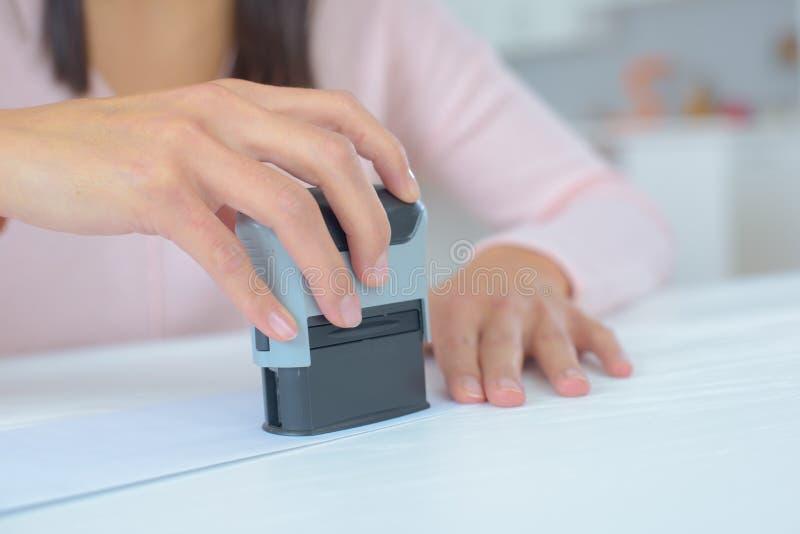 Vrouw die wettelijk document stempelen stock fotografie
