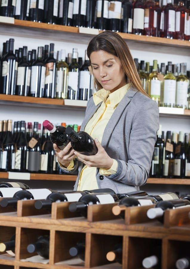 Vrouw die Wijnflessen bekijken in Opslag stock foto