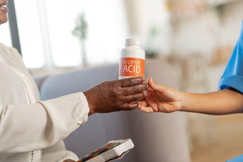 Vrouw die witte blouse draagt die pak met vitaminen van verpleegster neemt stock afbeeldingen