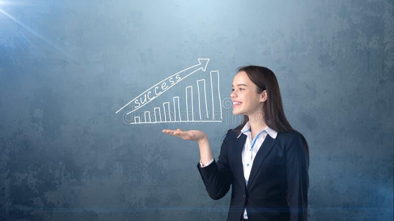 Vrouw die witte geschilderde het groeien grafiek met succeswoord houden op de open handpalm, geïsoleerde achtergrond Bedrijfs con stock fotografie