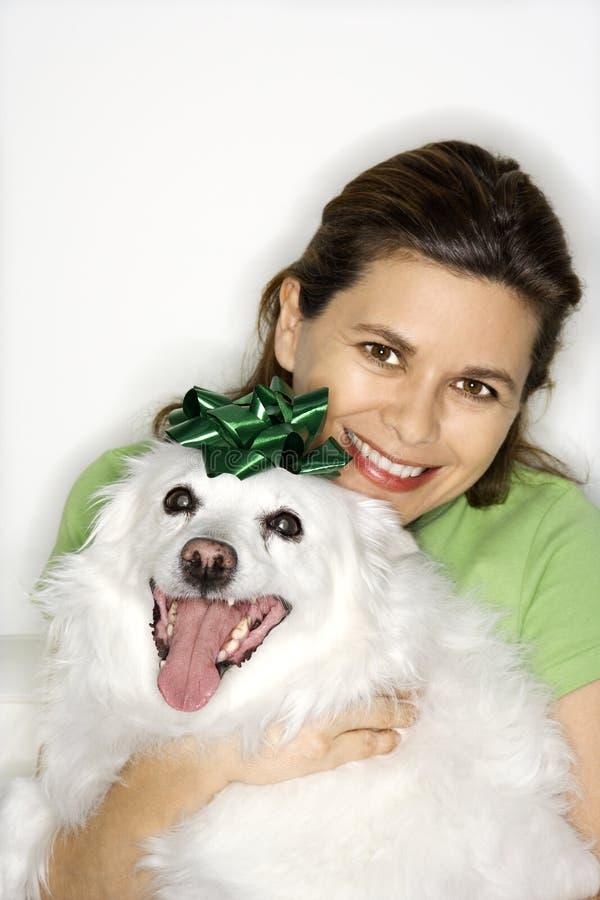 Vrouw die witte hond houdt. stock fotografie