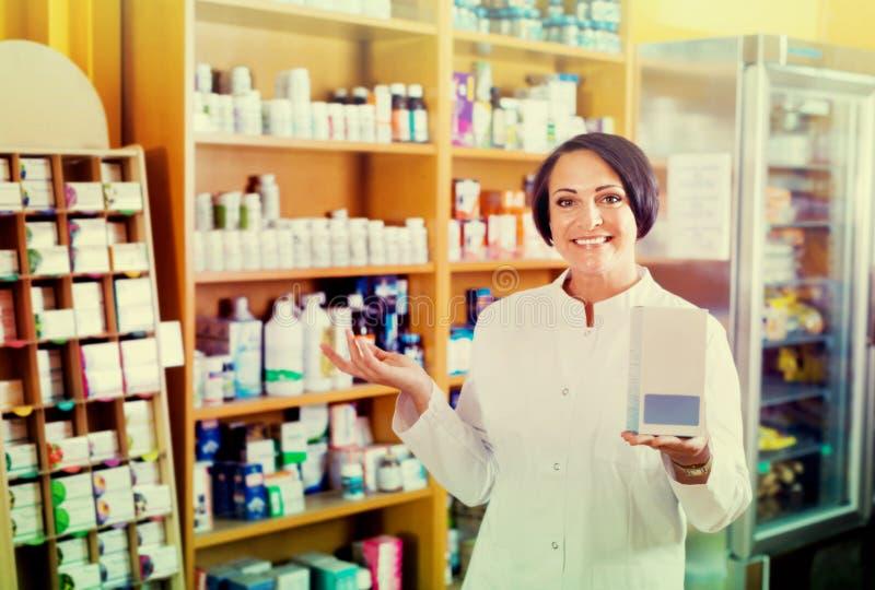 Vrouw die in witte laag additief voor levensmiddelengoederen in karton in D bevorderen royalty-vrije stock afbeelding