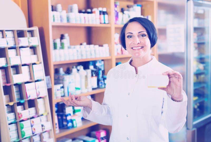 Vrouw die in witte laag additief voor levensmiddelengoederen in karton in D bevorderen stock foto